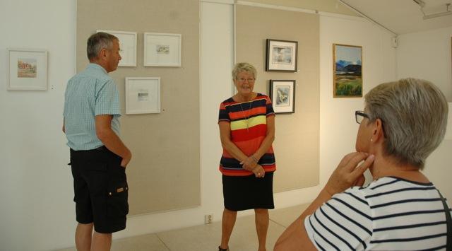 Monica Malmqvist (i mitten) samtalar om sin konst med några utställningsbesökare.