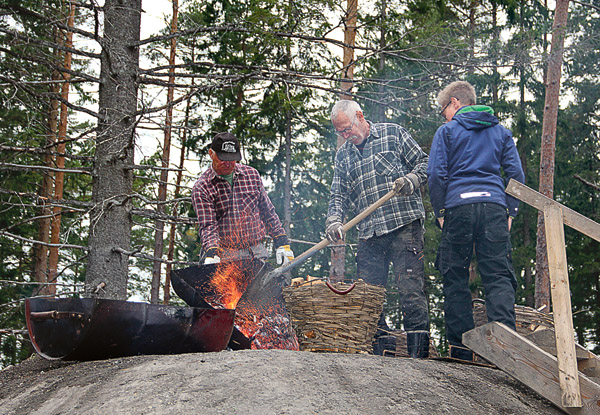 Sven Nilsson tömmer i glöden i mittentrumman medan Kennet Andersson rakar i och Robban Stenberg ser på. Det kom gott om nyfikna besökare till Kärnskogen i Godegård när kolmilan, döpt efter Svens fru Gun, skulle tändas.