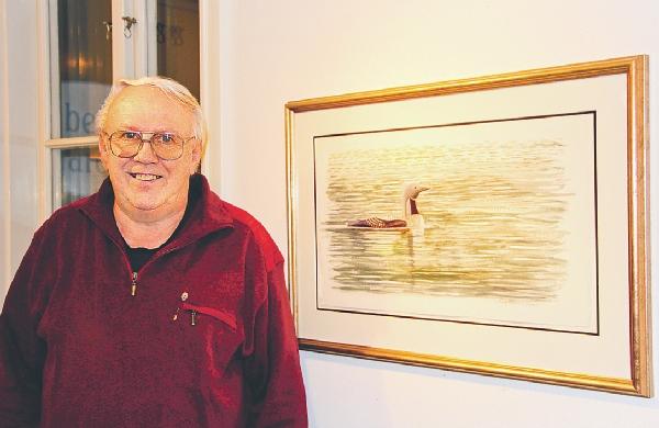 Greger Johansson med en av tavlorna som föreställer en storlom. Han målar i akvarell och olja men även exempel på digigrafik kunde ses på utställningen.