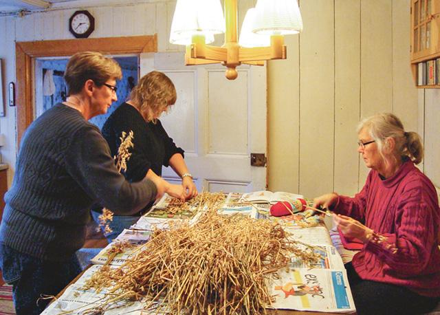 Anita klipper halm medan Mona och Annelie tillverkar stjärnor.