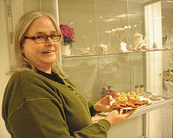 """Virkerskan Kerstin Karlsson plockar fram """"fikat"""" ur en monter på biblioteket i Horn. Lussekatter och pepparkakor, men här frestar även lakritskonfekt, kakor, bakelser och en tårta."""