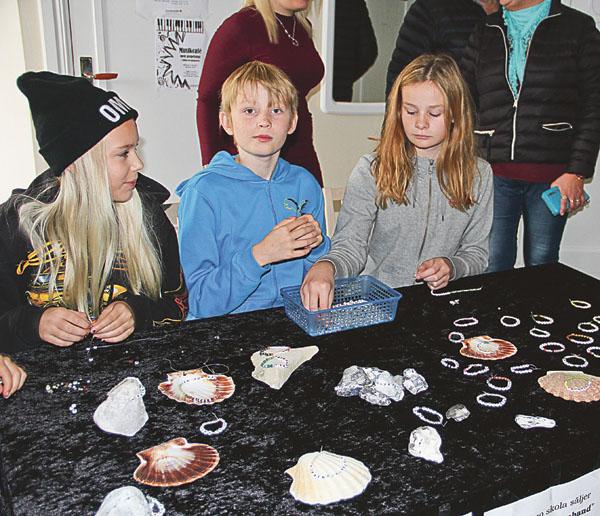 """Wilma Karlsson, Ruben Gustafsson och Alice Eriksson samt Frida Karlsson (ej i bild) klass 5-6 från Tjällmo skola satt och gjorde armband """"lika – unika"""" till förmån för UNHCR."""