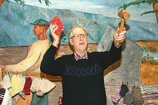 Hans Ivarsson håller i klubban på syföreningsauktion i Rök. En auktion som innehåller det mesta, dock inte så mycket sytt.