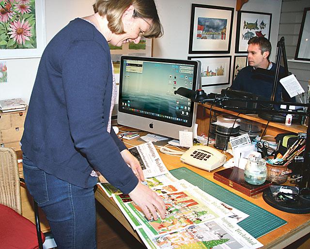 Cathrin Hesselstrand visar några av sina framsidor i Grönköpings veckoblad, Johan sitter vid sin arbetsplats. Sedan 2003 är huset Frukthem i Vadstena bostad och arbetsplats för familjen Hesselstrand.