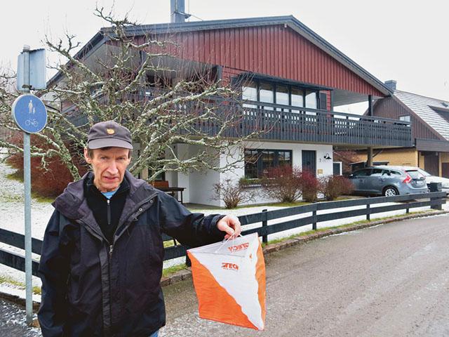 Håkan Gustafsson med en orienteringsskärm i handen och framför hans och Carinas villa på Björkstigen i Boxholm.