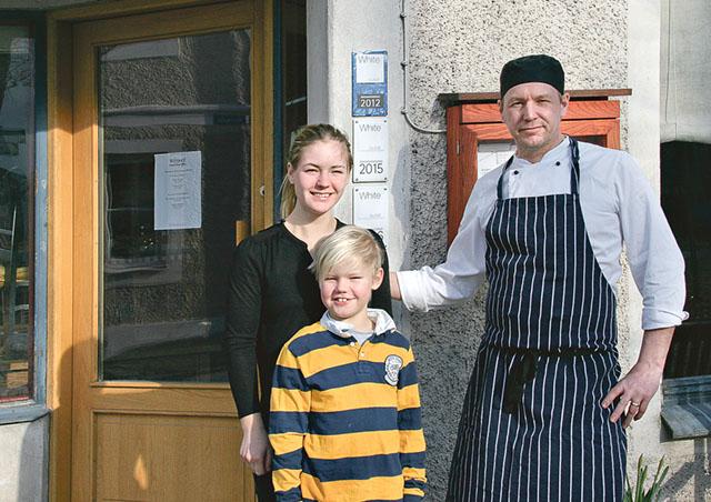Malin Unéus, sonen Julius Unéus och sambon Fredrik Gustafsson utanför sin restaurang.