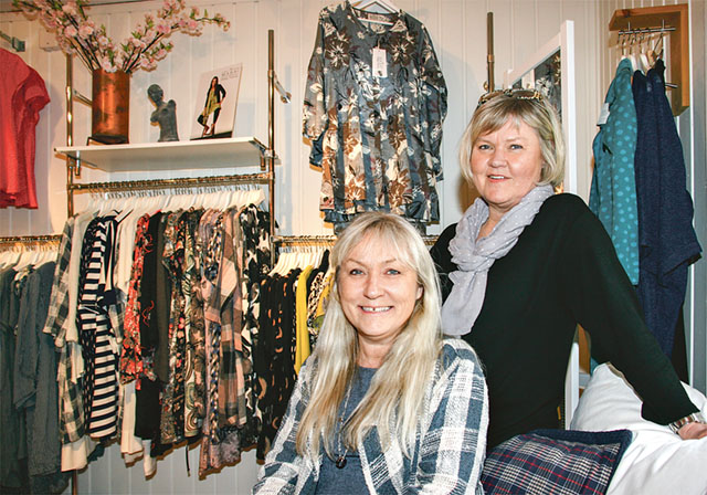Eva Granlund och Helena Andersson bland butikens kläder.