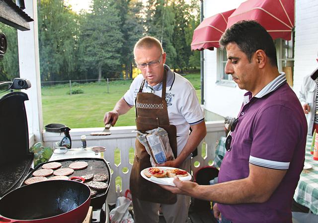 Nisse Graan (KD), kvällens grillmästare, serverar Thaer Tomeh en nygrillad hamburgare.