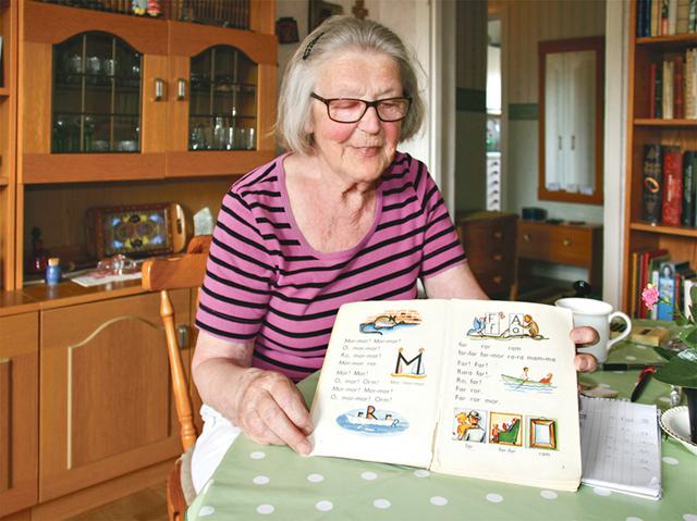 Barbro Dahlin visar en bok som hon använder när hon lär flyktingar läsa.