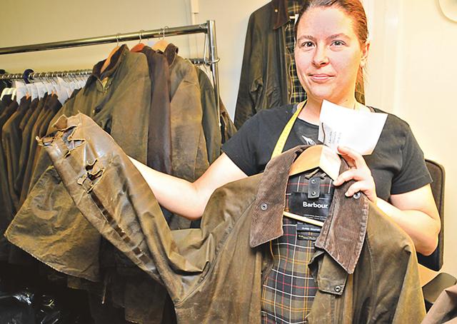 Sandra Heidenreich håller upp en Barbourjacka som ska lagas.
