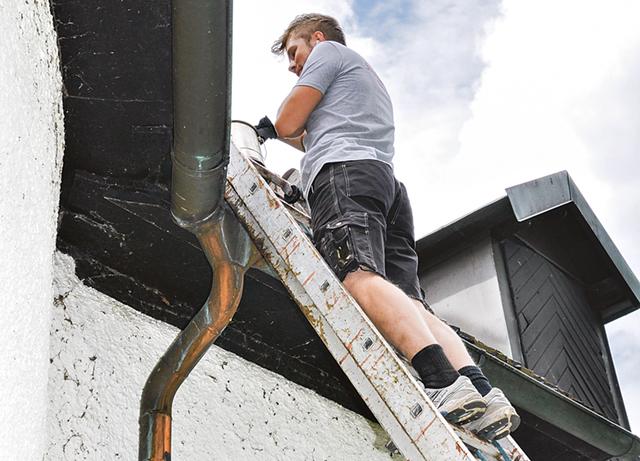 Christoffer Svensson tjärar taket. Han tycker det känns osäkrare att stå på stegen än att hänga i en sele högt uppe i kyrktornet