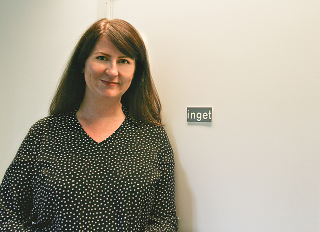 """Maria Jönsson, kulturstrateg i Vadstena, gillar dörrskylten med texten """"inget"""" i kommunhuset."""