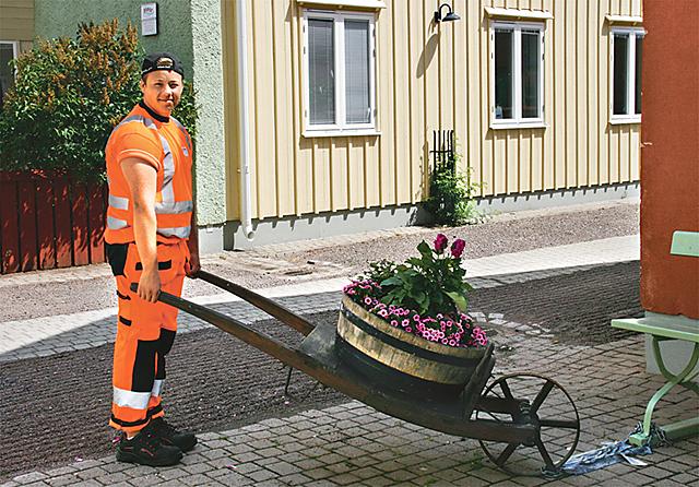 Gustav Johansson, kommunal feriepraktikant i Vadstena, ställer en blomsterkärra rätt.
