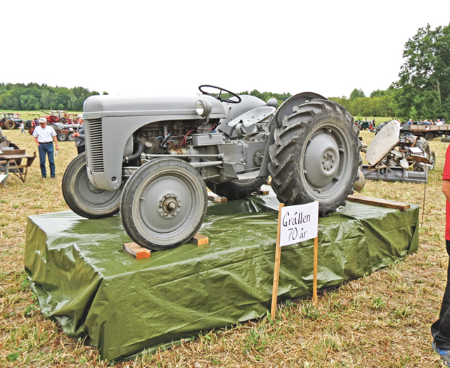 """På en tribun står """"Grålletvåan"""", den Grålle som har tillverkningsnummer två och var den första serietillverkade traktorn som lämnade fabrik."""