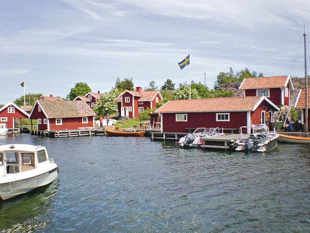 En sommaridyll med röda stugor, bryggor och båtar.