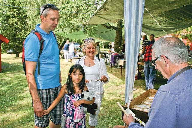 John Drakenberg och Sonja Dahlgren med dottern Sofia handlar en ihålig slev av träsnidare Börje Olsson.