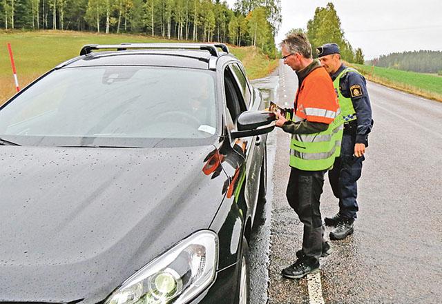 Per Gustavsson ger information och delar ut markeringsremsor till en bilist, sedan Karl Landström, kollat körkort och utfört nykterhetskontroll.