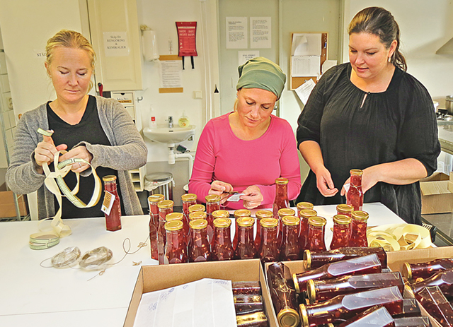 Annika Lindström, Malin Norman och Frida Knape håller på att etikettera flaskor med den Sweet Chili-sås som belönades med guldmedalj vid SM i svenskt mathantverk som i år avgjordes i Umeå.