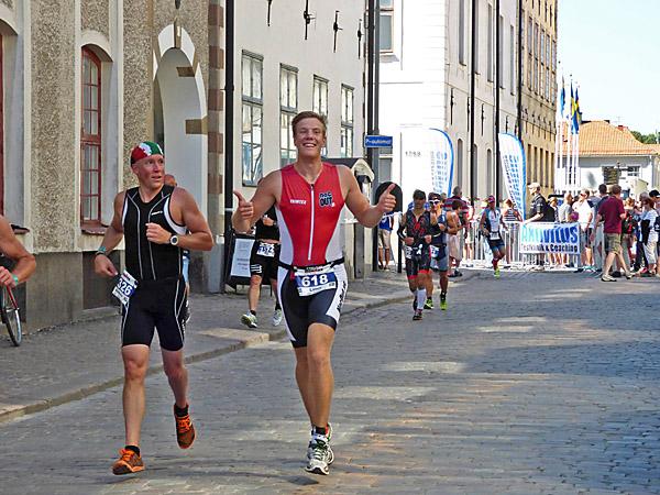 """Här springer Linus johansson fram på gatan i Kalmar mot det hägrande målet i Ironman. Han till vänster tycks undra, """"var får han alla krafter ifrån?"""""""