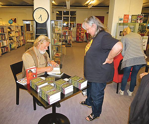 """Conny Larsson presenterade sin tredje bok, """"Nu ska jag upp och skjuta den jäveln! Olof Palme"""", på biblioteket i Valdemarsvik. Här signerar han sina böcker."""