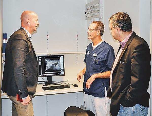 Magnus Oscarsson (till vänster) och Andreas Ardenfors lyssnar på veterinären Sven Ödman (mitten).
