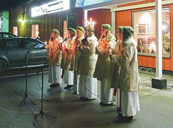 Lucia, Wilma Gustavsson, med sina tärnor sjunger utomhus på Vammarområdet.