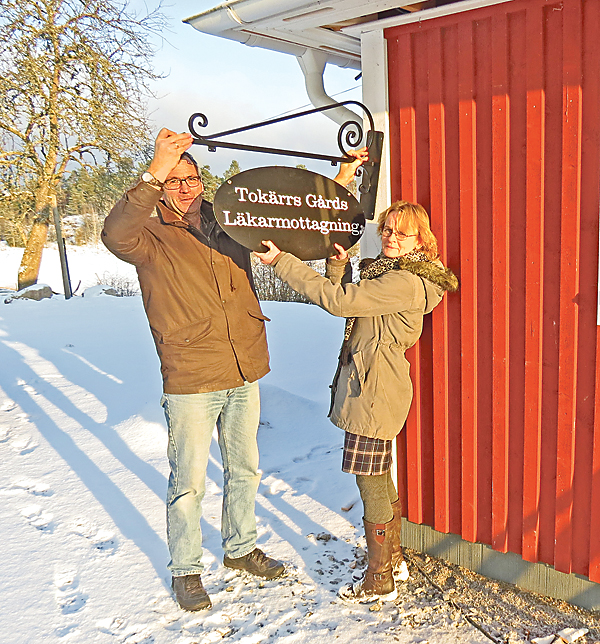 Lillemor och Niklas Högerås är i full färd att sätta upp skylten till den nya läkarmottagningen vid Tokärrs Gård, i Rullerum utanför Valdemarsvik.