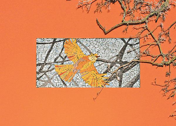 Två konstverk i modern mosaik med kanariefåglar pryder fasaden på äldreboendet i Sandrinoparken