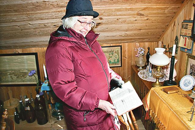 Margareta Hesslevad i gårdsmuseets övervåning. Här visar hon en almanacka från 1936 där dagens inköp har noterats.