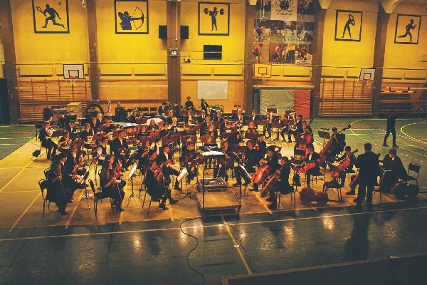 Alla 63 orkestermedlemmarna har intagit sin platser och väntar på att dirigenten Cecilia Rydinger Alin, rektor på Musikhögskolan i Stockholm, ska inta dirigentpulpeten så att konserten kan börja.