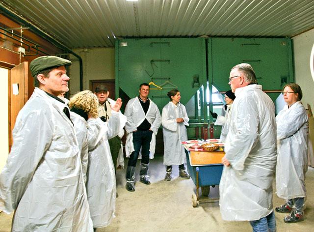Alla deltagare får klä sig i skyddskläder av plast innan de kommer in i stallet.