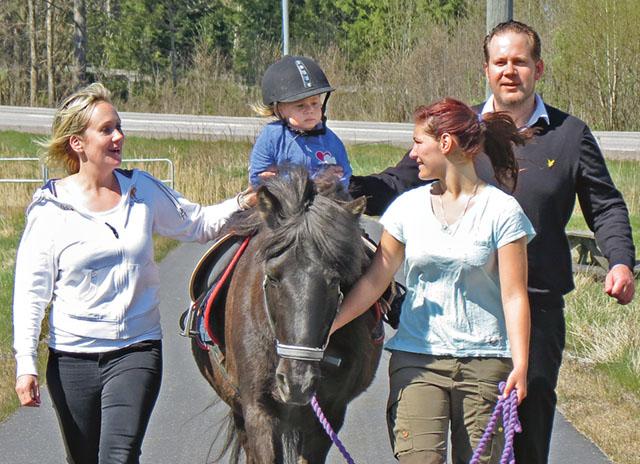 En stolt liten ryttarinna, Emelie Löfgren, sitter säkert i sadeln och får stöd av mamma Julia och pappa Henrik. Leder hästen gör Emelie Ferm, från Hästbutiken.