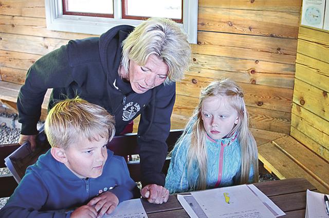 Läraren Mia Karlsson kontrollerar vad Nils Magnusson och Tyra Persson jobbat med.