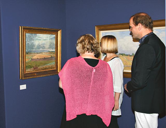 Kristina Lohman, Cecilia Lindheimer och Göran Fältgren funderar över målningen Vetet skördas, målad av Prins Eugen 1930.