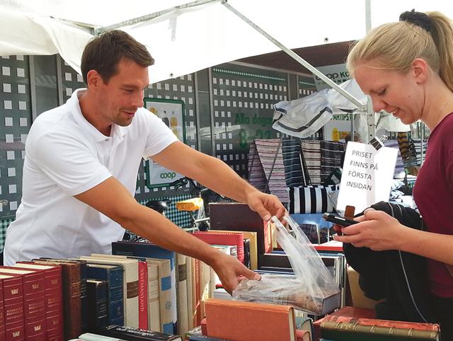 Mattias Svanström säljer en bok till Linnea Eriksson.