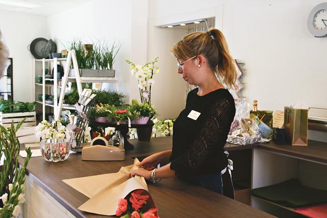 Frida Rydberg slår in några gladiolus till en kund.