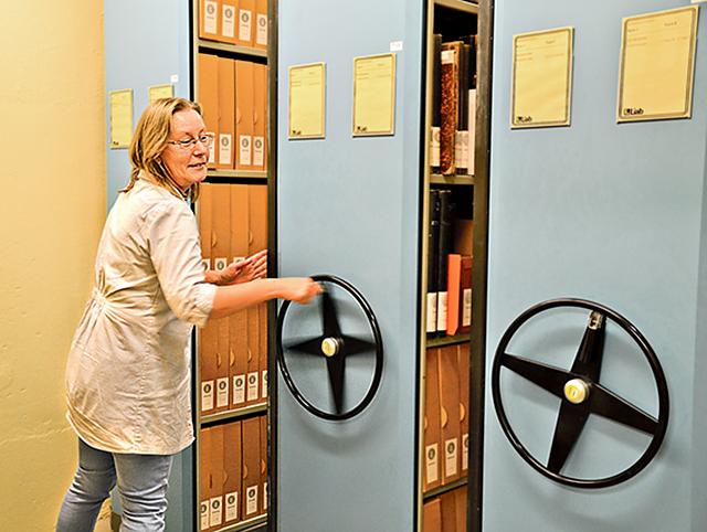 Pernilla i färd med att plocka fram en låda med kartotek som en forskare vill ta del av.