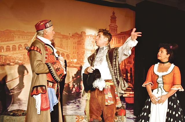 Betjänten Truffaldino (Mattias Schönbeck) verkar mycket upprörd inför köpman Pantalone (Mats Huddén). Kammarjungfrun Smeraldina (Carolin Albrecht) avvaktar.