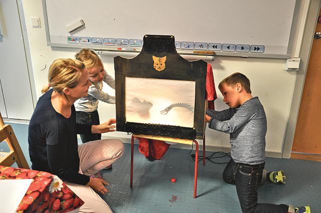 Mamma Elin med Ester och Ebbe som testar sin fjäril respektive drake i teatern.