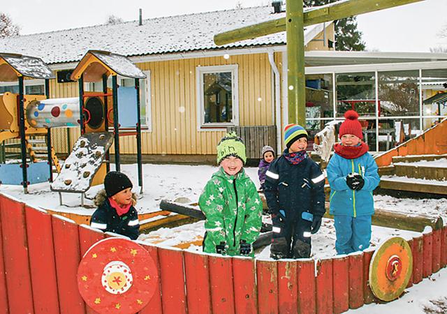 Tyra, Albin, Frans och Alva i en båt på gården. Tyras lillasyster Elsa tittar fram bakom.